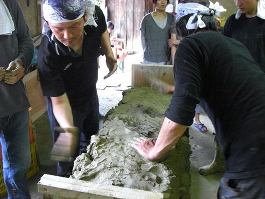 昔ながらの瓦製法たたら作りをする職人と見学する関西大学の学生
