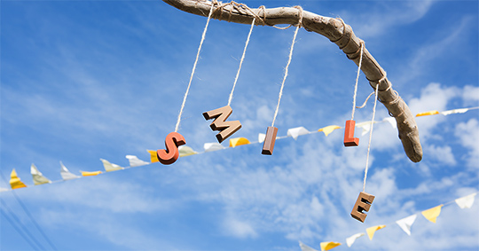 青空の下に切り文字商品VASARA TERRAを流木に結びつけたモビールSMILEの文字が揺れる