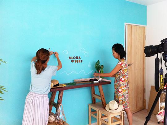 水色の壁にVASARA TERRAのALOHA SURFの切り文字を貼り付ける女性二人