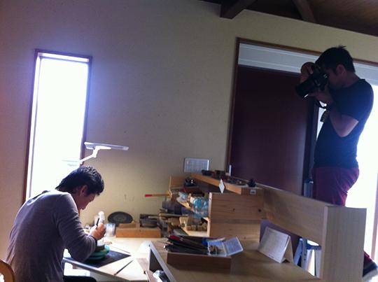 切り文字を彫る職人を撮影するカメラマン