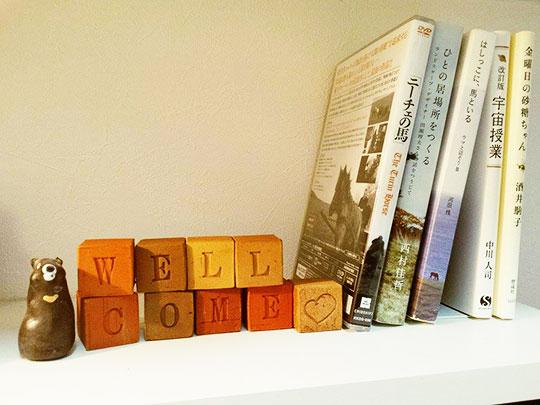 本棚に飾られたメッセージ雑貨、キューブ煉瓦、WELL COMEの文字とハートマーク